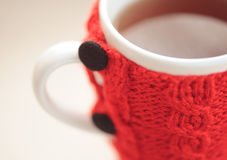 Knitted cup closeup. Closeup red knitted cup of tea, selective focus Stock Photo