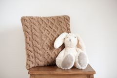 Knitted cushion of natural shade in the interior. With a toy stock photo