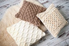 Knitted cushions of natural shades. On sheep`s clothing Royalty Free Stock Images