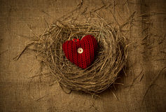 Knitted decorative heart lying in birds nest on linen cloth Stock Photo