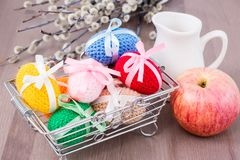 Knitted Easter eggs tied with colored ribbons in a metal basket, an apple, a jug and willow. On a wooden table royalty free stock photos