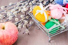 Knitted Easter eggs tied with colored ribbons in a metal basket, an apple and willow. On a wooden table royalty free stock images