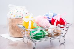 Knitted Easter eggs tied with colored ribbons in a metal basket and Easter cake. On a wooden table royalty free stock photos