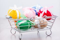 Knitted Easter eggs tied with colored ribbons in a metal basket. On a wooden table royalty free stock photography