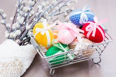Knitted Easter eggs tied with colored ribbons in a metal basket and willow. On a wooden table royalty free stock photography