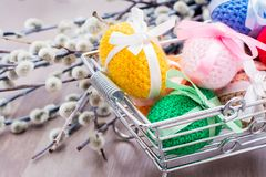 Knitted Easter eggs tied with colored ribbons in a metal basket and willow. On a wooden table royalty free stock image