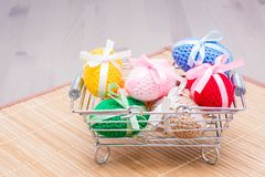 Knitted Easter eggs tied with colored ribbons in a metal basket. On a wooden table stock photos