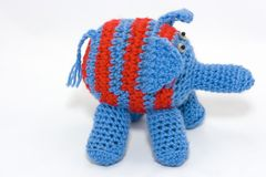 Knitted elephant. Knitted blue elephant with red stripes Stock Photo