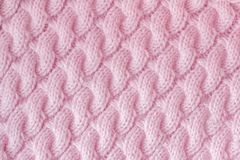 Knitted fabric made of wool yarn pink color. Pattern. `spit` associated knitting needles, handmade. Background texture Royalty Free Stock Photography