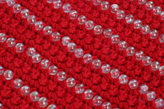Knitted fabric of red color with the decor of beads royalty free stock image