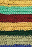 Knitted fine wool garment colorful stripes background natural texture, yellow, beige, claret, blue, green scarf macro closeup Royalty Free Stock Photo