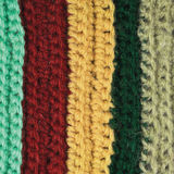 Knitted fine wool garment colorful stripes background natural texture, yellow, beige, claret, blue, green scarf macro closeup Stock Image
