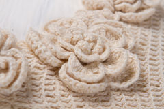 Knitted flower on beige cloth. Stock Image