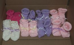 Knitted Girl Baby Booties with Ribbons Lined Up in a Row - Colors: Pink, Purple, White stock photo