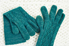 Knitted green gloves on white scarf Royalty Free Stock Photography