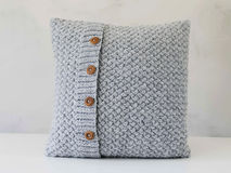 Knitted grey pillow with wooden buttons Stock Photos