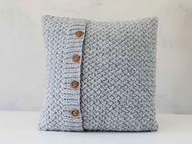 Knitted grey pillow with wooden buttons Royalty Free Stock Photography