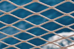 Knitted grid on boat banister with blurred sea on background Stock Image