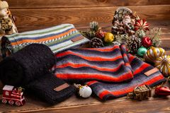 Knitted ha barrato le sciarpe a strisce, le maniche tricottate nere ed i giocattoli di Natale su fondo di legno fotografia stock libera da diritti