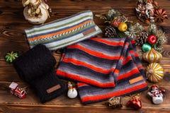 Knitted ha barrato le sciarpe a strisce, le maniche tricottate nere ed i giocattoli di Natale su fondo di legno immagini stock libere da diritti