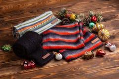 Knitted ha barrato le sciarpe a strisce, le maniche tricottate nere ed i giocattoli di Natale su fondo di legno immagini stock