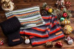 Knitted ha barrato le sciarpe a strisce, le maniche tricottate nere ed i giocattoli di Natale su fondo di legno immagine stock libera da diritti
