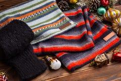 Knitted ha barrato le sciarpe a strisce, le maniche tricottate nere ed i giocattoli di Natale su fondo di legno fotografie stock libere da diritti