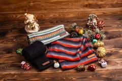 Knitted ha barrato le sciarpe a strisce, le maniche tricottate nere ed i giocattoli di Natale su fondo di legno immagine stock
