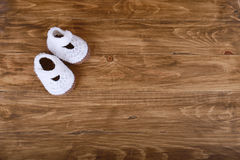 Knitted handmade baby shoes on wood background Stock Photos