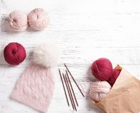 Knitted handmade hat on a white wooden background Royalty Free Stock Photo