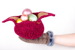 Knitted hat with Christmas decorations on hand Stock Photo