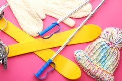Knitted hat and mittens with ski outfit. On color background. Winter vacation concept stock photography
