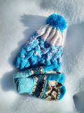Winter clothes, knitted hat and mittens in the snow royalty free stock photography