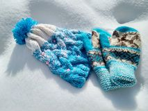 Winter clothes, knitted hat and mittens in the snow stock photos