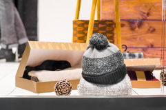 Knitted hat  with pompons in a store showcase Royalty Free Stock Photo