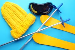 Knitted hat with ski outfit on color background. Winter vacation concept royalty free stock photos