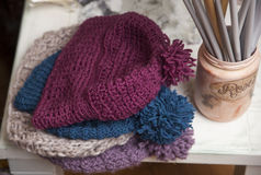 Knitted hats. Of different colors on a white table with handmade decoupage bottles stock photos