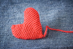 Knitted heart on blue jeans texture background Stock Photography