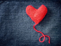 Knitted heart on blue jeans texture background Stock Photo