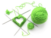 Knitted heart on needles with yarn. A knitted heart on four needles with yarn Stock Photos