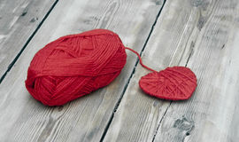 Knitted heart and red of yarn Stock Images