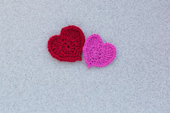 Knitted hearts. On a white wooden background Royalty Free Stock Images