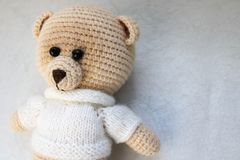 A knitted homemade beautiful cute little bear in a white sweater with black eyes, a soft toy tied with beige large threads on a li royalty free stock photos
