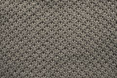 Knitted honeycomb texture of dark beige color Stock Photos