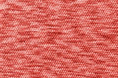 Knitted Jersey fabric textile trendy colored of the year 2019, coral color background, texture stock photography