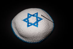 Knitted kippah with blue David star on black background close up. Seder concept Stock Photography