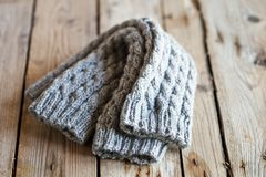 Knitted light grey leg warmers. On wooden background stock images