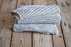 Knitted light grey scarf. On wooden background stock images