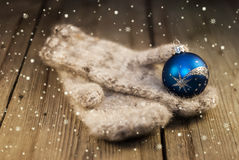 Knitted mittens and Christmas decoration on wooden background Stock Photo