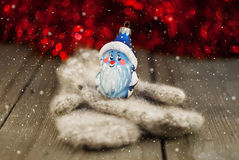 Knitted mittens and Christmas decoration on wooden background Stock Images